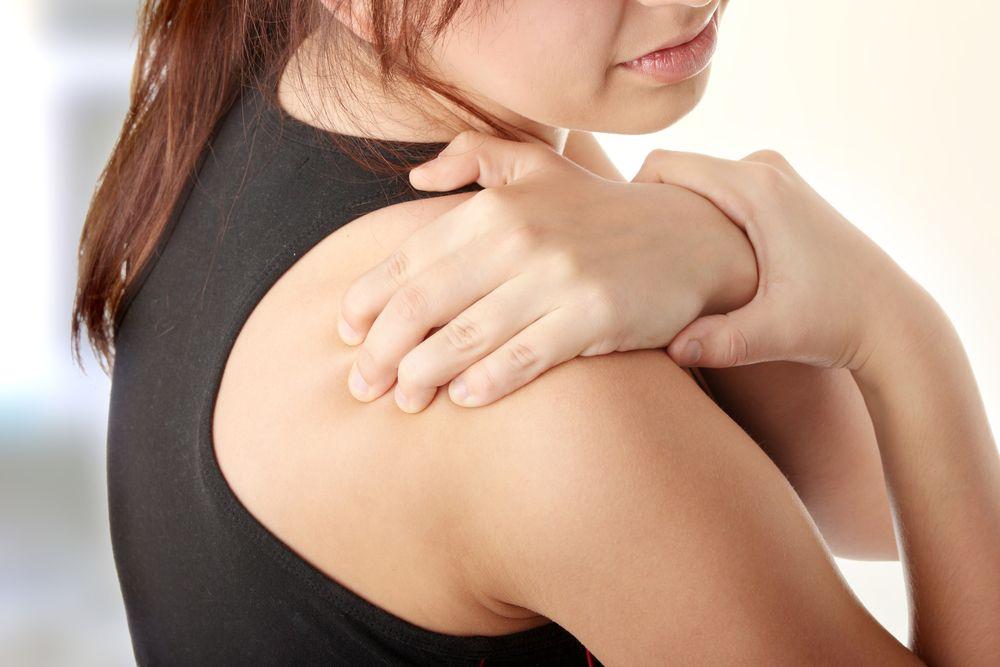 Боль в плече, человек держится за плечо
