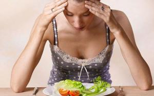 девушка сидит над тарелкой с овощами