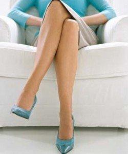 Женщина сидит, закинув ногу на ногу