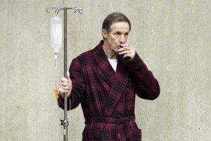 Человек курит возле больницы с капельницей