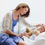 женщина сидит на кровати больного ребенка