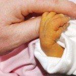ребенок с желтухой держит на палец человека