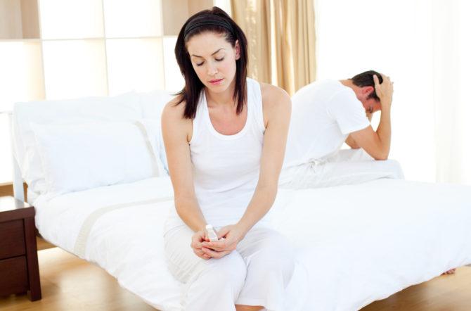 Грустный мужчина и женщина с тестом на беременность