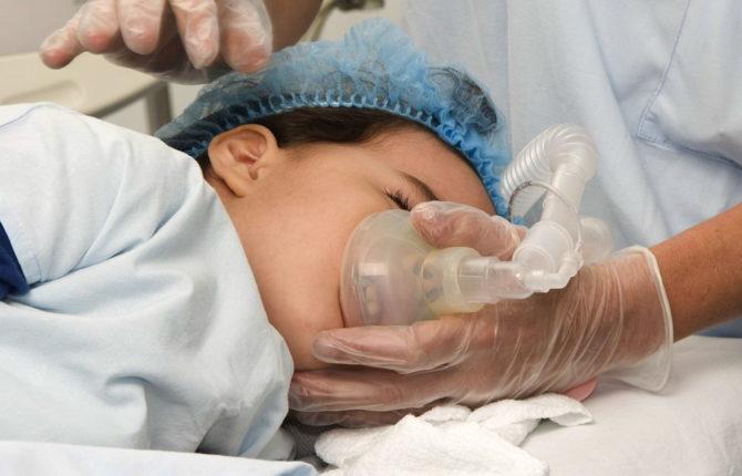 Ребенок дышит через кислородную маску