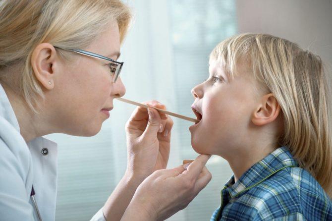 Врач осматривает горло ребёнка
