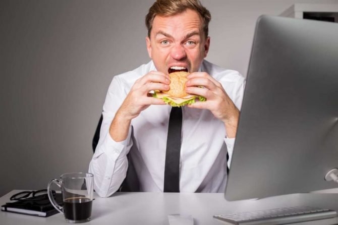 Мужчина ест за компьютером