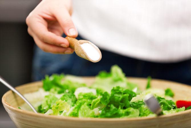 Женщина солит салат