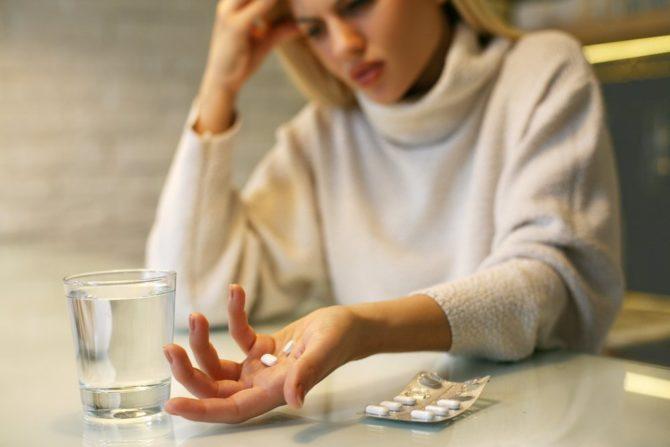 Женщина сидит за столом и держит в руке таблетки