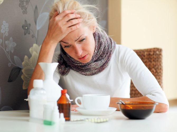 Заболевшая женщина сидит за столом с лекарствами и держится за голову