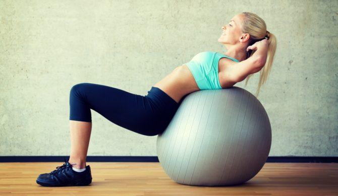 Девушка выполняет упражнение на фитболе