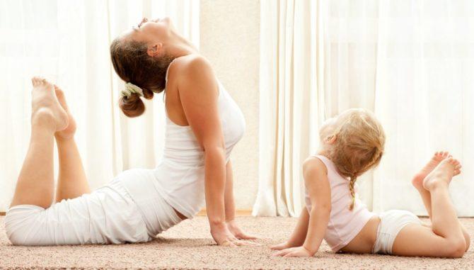 Мама и дочь выполняют гимнастическое упражнение