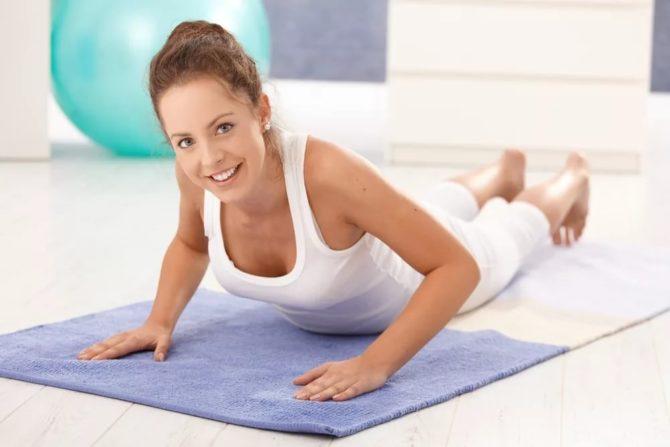 Девушка выполняет упражнение на коврике