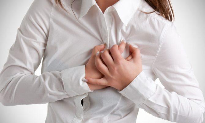 Женщина держит руки на области сердца