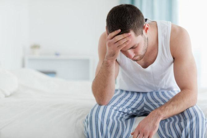 Мужчина сидит на краю кровати