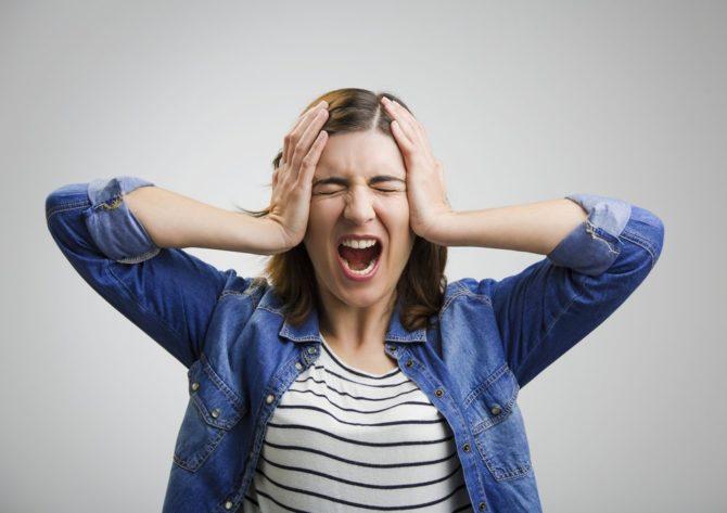 Девушка кричит, схватившись руками за голову