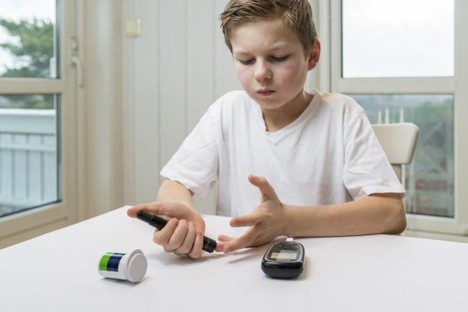 Мальчик измеряет уровень сахара в крови