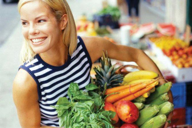 Женщина несёт овощи и фрукты