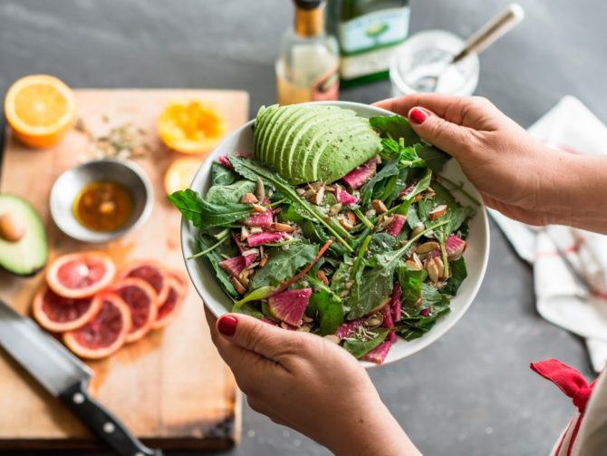 Тарелка с салатом в руках у женщины