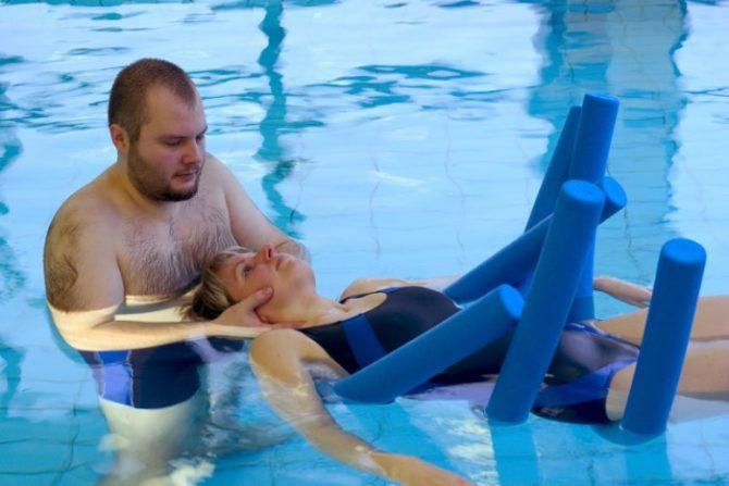 Женщина делает упражнения в бассейне
