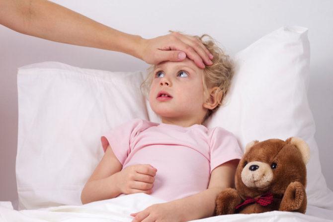 Ребёнок лежит в постели с повышенной температурой