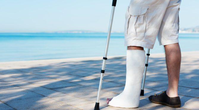 Мужчина в гипсовой повязке на ноге у берега моря