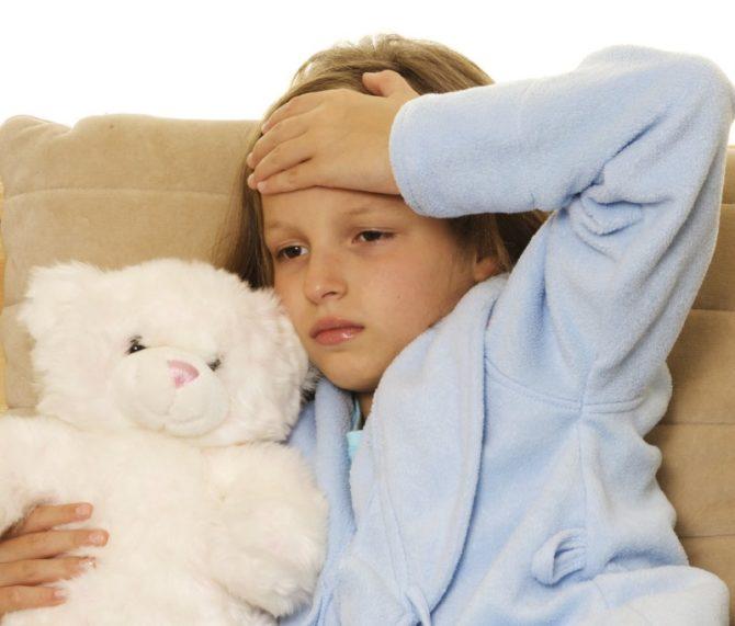 Ребёнок с плюшевым мишкой держит руку на голове