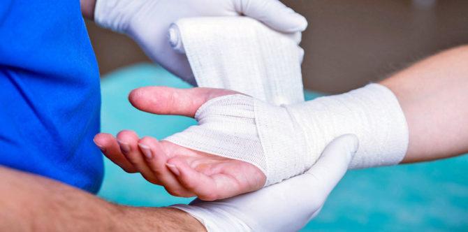 Врач бинтует руку пострадавшему