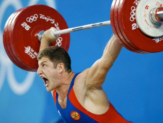 Спортсмен поднимает тяжёлую штангу