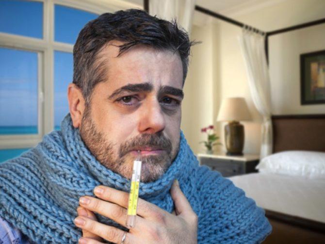 Больной мужчина с градусником во рту