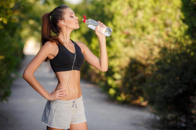 Девушка пьёт воду на ходу